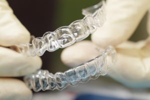 Close up image of a dentist holding a set of clear bite guards