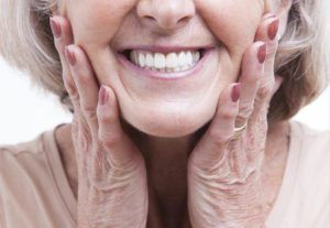 Elderly woman with dentures, smiling, with her ands on her cheek