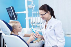 Female dentist treating child seated in a dental chair